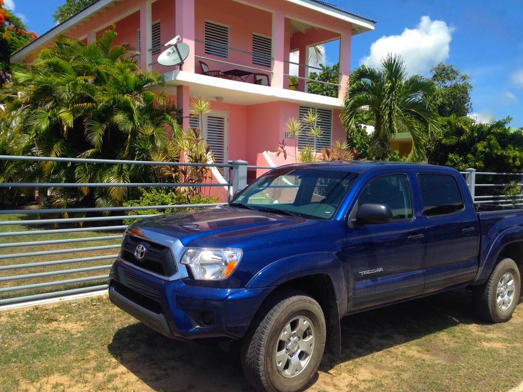 dark blue, four-door, 2015 Toyota Tacoma parked in front of the decorative wall in front of the pink house